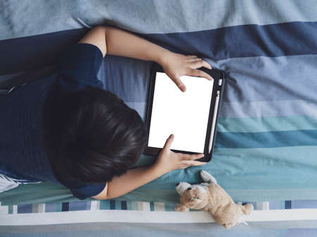 Kid wathching cartoons on tablet, Child boy lying in bed playing game on touch pad, Top view Children having activity on his own in bedroom with mock up of digital tablet. New normal life education