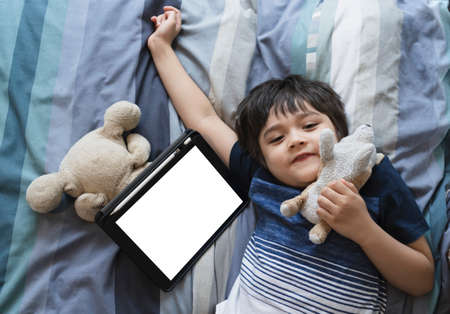 Kid laying in bed playing with soft toy and looking at cameara with smiling face, Child boy lying in bed with tablet, Top view Children having activity on his own in bedroom with mock up of digital tablet. New normal life education