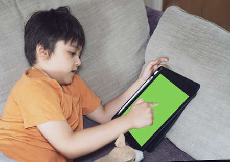 Kid lying on sofa playing game on tablet, Child boy relaxing at home drawing or wring on digital pad, Children avtivity for new normal life education or Distance learning concept