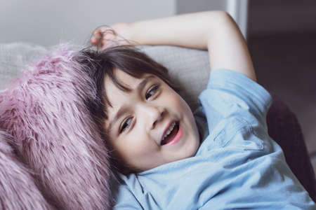 Healhty kid smiling face lying head on fulffy cushion, Happy child boy relaxing at home enjoying time on his own. Positive children concept 版權商用圖片