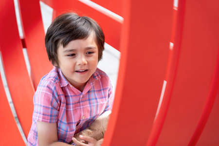 Happyy kid sitting on red chair, Healthy child playing with outdoor metal chair, Young boy having fun playing outside in spring or summer day, Positive children concept
