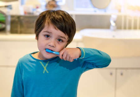 Portrait little boy burshing teethe with sleepy eyes, Kid wearing pajamas with tired face cleaning his teeth in the morning, Children health care concept