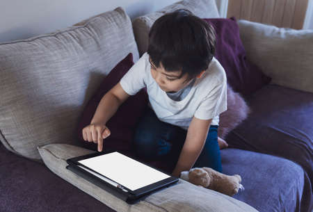 Cropped shot kid sitting on sofa watching cartoons on tablet,6-7 year old boy playing game on touch pad, Cute Kid having fun and relaxing on his own in living room, New normal lifestyle 版權商用圖片 - 151323993