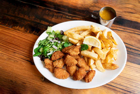 Home made scampi and chips served with mixed vegetables salad and lemon on top, English traditional menu, fresh food,selective focus 版權商用圖片 - 151484273