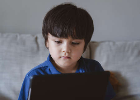 School Kid using tablet for his homework, Child looking at digital tablet with thinking face, Young boy watching cartoon on touch pad, nw normal life stye with learning online, Distance education 版權商用圖片