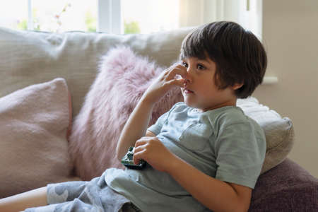 Kid lying on sofa scratching his nose while watching TV,  Child feeling itchy on his nose from fluffy cushion, Young boy relaxing at home on his own in weekend. Positive children concept 版權商用圖片
