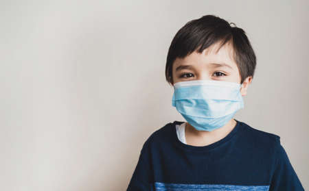 Portrait kid face wearing medical face mask, Mixed race child boy with beautiful brown eyeswearing blue face mask looking at camera, Little boy stay at home during covid-19 lock down.