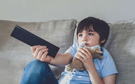 Kid sitting on sofa holding remote control and watching cartoon on TV, Child boy stay at home relaxing in living room during covid 19 lockdown, Social Distancing