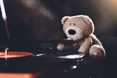 Still life wiith shafts of morning light stream through lonely teddy bear sitting on spinning record vinyl player, Low key light image Brown bear sitting alone in drak room.