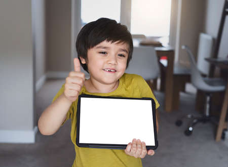Selective fouc happy 6-7 year old kid with smiling face holding tablet and showing thumb up, New normal life, child boy using tablet learning at home, Home schooling,E-learning online education 版權商用圖片 - 151808708