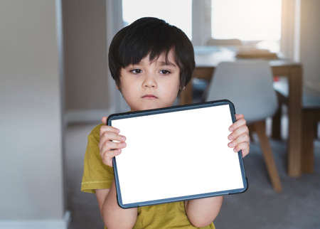Selective fouc sad 6-7 year old kid with bored face holding tablet.  New normal life, child boy using tablet learning at home, Home schooling,E-learning online education