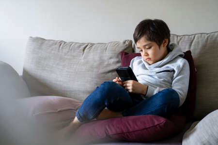 Child boy sitting on sofa watching cartoons on mobile  phone, School kid using cellphones learning lesson on internet, Home schooling, New normal Distance learning online education