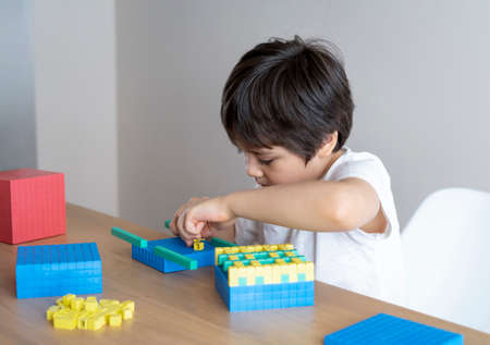 School kid using plastic block counting number, Child boy studying math by colour stack box, Dienes or Montessori classroom material for children learning of mathematics at home, Home schooling