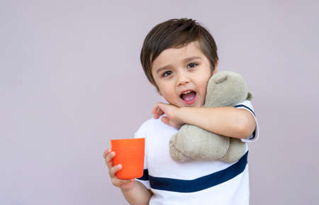 Studio portrait cute little boy drinking orange juice from plastic glass on light purple background, Healthy 4-5 year old boy drinking glass of mixed fruits juice and holding teddy bear 版權商用圖片