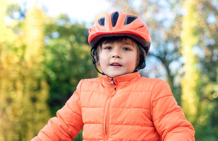 Portrait of Kid wearing helmet looking at camera with smiling face,   6-7 year old mixed race Asian-Caucasian boy wears a bike helmet standing  outside in the park, Child having fun outdoor in Autumn 版權商用圖片 - 152376205