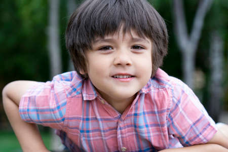 Healthy Kid relaxing in the park with blurry natural bokeh background, Cute little boy looking at cameara with smiking face. Head shot of happy child playing outdoors in spring or summer. 版權商用圖片 - 151970843