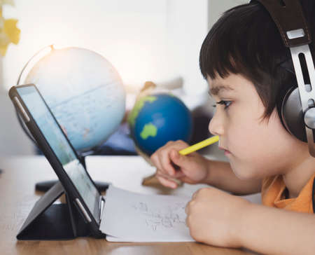Cropped shot Kid using tablet for his homework,Child using digital tablet searching information on internet during, Home schooling, Social Distance, E-learning online education