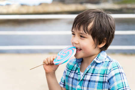 Funny kid eating  lollipop, happy little boy holding big sugar candy, Child with smiling face eat sweets, Active childhood enjoying funtime outdoor in sunny day summer 版權商用圖片 - 151970683
