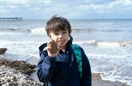 Kid with dirty mount of chocolate ice cream showing stone to the beach on spring or summer, Child boy playing with the rock, Children exploring by the seaside, Play and lean from nature 版權商用圖片