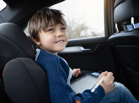 Happy young boy using a tablet computer while sitting in the back passenger seat of a car with a safety belt, Child boy drawing on smart pad,Portrait of toddler entertaining him self on a road trip. 版權商用圖片 - 151970711