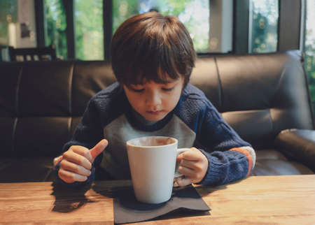 Candid shot kid drinking hot chocolate in the cafe with warm tone, Healthy child boy blowing hot drink at coffee shop in winter. 版權商用圖片