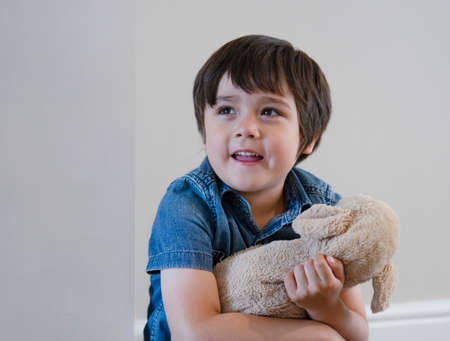 Portrait happy boy playing with dog toy on white background, Adorable Child with big smile playing with soft  toys relaxing at home. Positive children concept