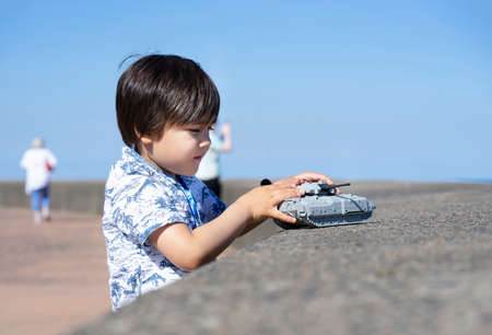 High key light little boy playing with soldiers and tank toys by the sea in hot sunny day summer, Kid playing wars and peace on his own with blurry sea beach background,Children development concept