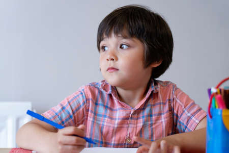 Portrait of school kid boy siting on table and looking out with thinking face, Child holding blue paint colour, Elementary school and education concept
