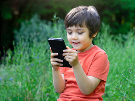 Outdoor portrait  kid with a happy face playing game on mobile phone, Cute boy having fun watching cartoons on phone, Kid with smiling face playing games, 版權商用圖片
