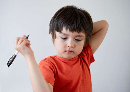 Portrait Kid boy holding black pen sitting alone and looking down with bored face ,Lonely child looking d down at table with sad face,Five years old kid bored with school homework,spoiled child