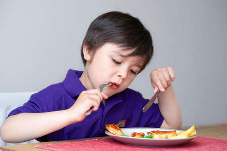 Healhty kid eating homemade salmon steak and chips for his sunnday dinner at home, Portrait of Child boy learning how to use knife and fork by him self, Healthy food for Children concept