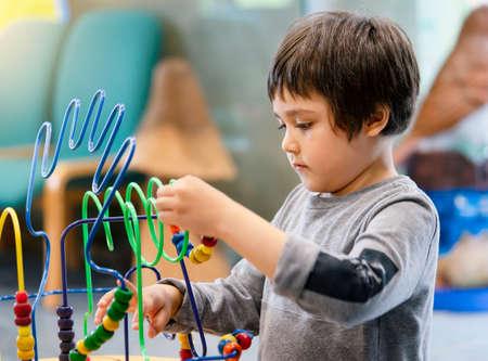 Indoor Portrait preschool boy playing in kid club with vintage tone, Child having fun playing colorful toys in kid playroom. Kid boy playing with educational toys in kindergarten. Education concept 版權商用圖片