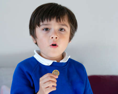 Portrait school kid showing one pound coin on his hand with proud face after back from school, Child boy wearing school uniform holding money coin, Child learning about saving concept 版權商用圖片
