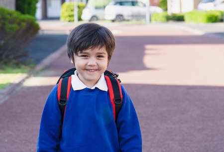 Outdoor portrait of happy child boy with backpack, School kid waiting for school bus, Pupil of primary going to school,Young student beginning of class after school holiday,Back to school concept