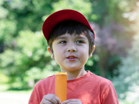 Portrait kid eating ice lolli with blurry nature background, Happy little boy standing in the park enjoy eating ice cream lolli pop in hot sunny day summer.