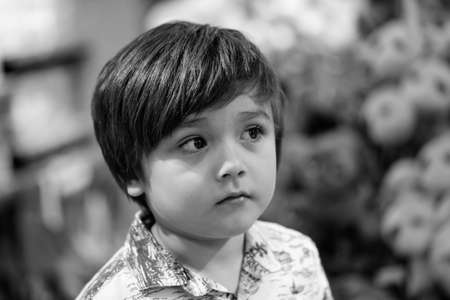 Black and white photo of Head shot kid sad face looking up with blurry toys shop background, Portrait Child with upset face standing in the shop. Spoiled children concept 版權商用圖片