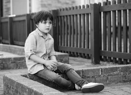 Outdoor portrait of little boy looking out with thinking face, Child playing outdoor activity.
