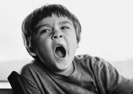 Close up face of Kid yawning lying , Sleepy child yawning and looking down, Black and white Indoor portrait tired child get a cold during weather change, Children health care concept
