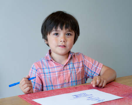Portrait of school kid boy siting on table doing homework, Happy Child holding blue colour paint,A boy drawing blue colour on white paper at the table,Elementary school and education concept 版權商用圖片 - 152069307