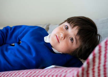 Portrait school kid lying on sofa watching TV after back from school, Adorable Child laying down on couch relaxing in playroom at home