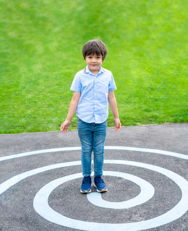 Full lenght portrait kid standing on circle line at asphalt, Active kid playing in green field at the park , Child play and learn outdoor activity con spring or summer 版權商用圖片 - 152055764