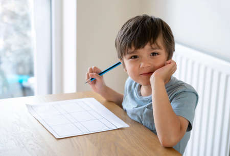 Portrait of school kid siting on table doing homework, Happy Child boy holding pencil and looking camera with smiling face, Elementary school and homeschooling concept 版權商用圖片 - 152132313