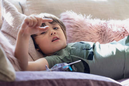 Selective focus happy boy lying on on sofa looking through his finger, High key light child relaxing at home on weekend,  Warm and cozy scene in  Pastel tone, 版權商用圖片