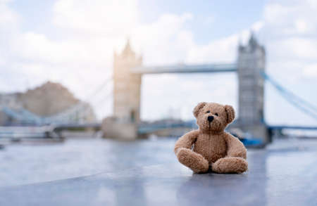 Teddy bear sitting alone with blurry london tower bridge background, The forgotten bear sitting by the river, lost property, Lonely concept, Lost child, International missing child