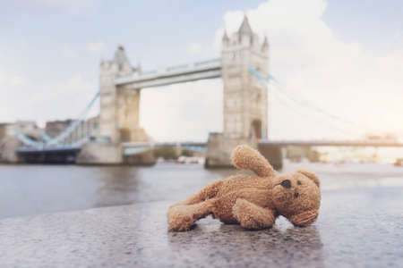 Teddy bear lying alone with blurry london tower bridge background, The forgotten bear sitting by the river, lost property, Lonely concept, Lost child, International missing child