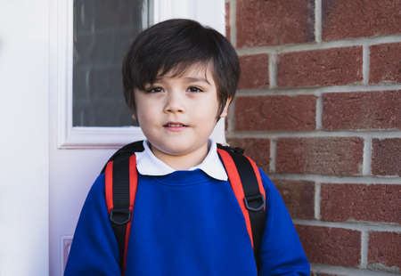 Outdoor portrait of happy child boy with backpack, Head shot of School kid wearing uniform,Pupil of primary going to school,Young student beginning of class after school holiday,Back to school concept