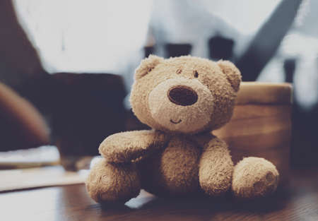 Soft focus of cute little bear sitting alone on table, Happy brown bear with blurry background in retro filter
