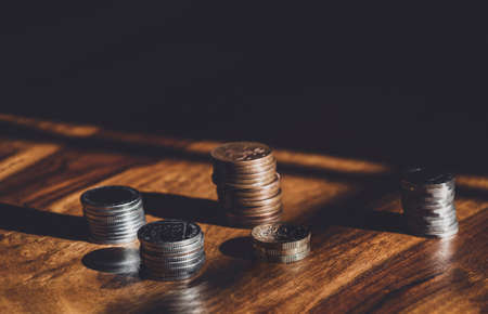 Stacks  British money pound coins on wooden table, Selective focus GBP coins on the floor with shadow and light in dark room, Business and financial for money saving or investment concept