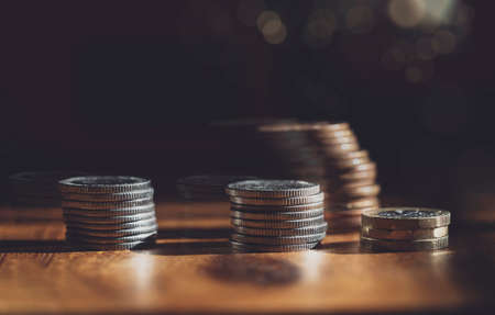Double exposure rows stack British money pound coins on wooden table in retro filter, Selective focus GBP coins  with shadow and light, Business and financial for money saving or investment concept
