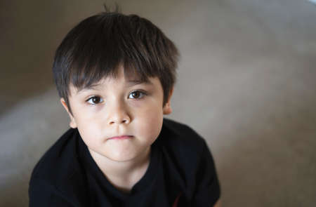 Top view head shot kid looking up with copy space, Candid young boy looking at camera with curiouse face, Child sitting on floor relaxing at home on weekend, Healthy and Positive children concept 版權商用圖片
